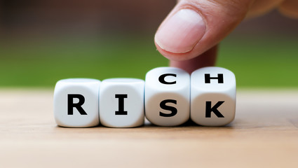 Take a risk and getting rich concept. Hand turns dice and changes the word