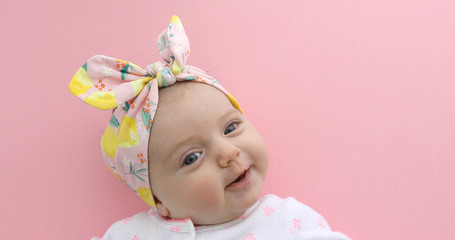 Newborn baby girl smiling in bow pink background