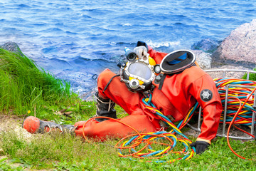 Diver in an orange suit sitting on the shore. Template for photoshop.