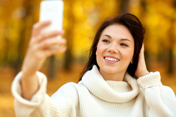 36e3f67fcc season, technology and people concept - beautiful young happy woman taking  selfie by smartphone at