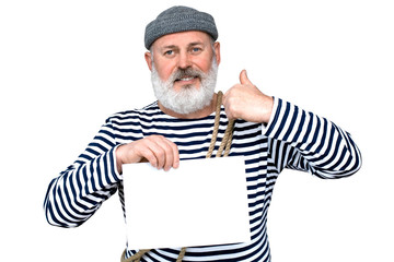 Photo sailor in a striped T-shirt. A middle-aged man with a gray beard is holding a white piece of paper