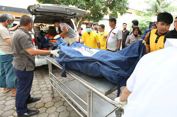 An officer helps transport a body bag containing a victim who died in a fire at a matchsticks factory, at Bhayangkara hospital in Medan