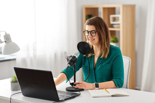 technology, mass media and people concept - woman in glasses with microphone and laptop computer talking and recording podcast at studio