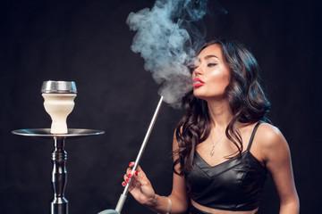 girl smokes hookah / beautiful glamorous girl in black dress smokes a hookah