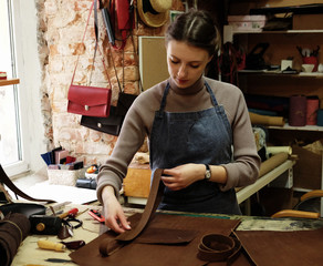 young woman works in a bag making studio, cuts out details