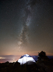 Tourist camping at summer night on the top of rocky mountain. Glowing tent under incredibly beautiful night sky full of stars and Milky way. On background starry sky, mountains and luminous town