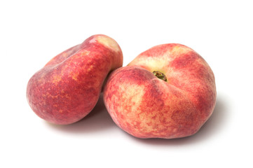 Closeup of organic flat peaches on white background