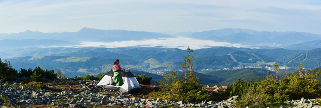 Panoramic view of camping on the top of mountain on summer morning. Back view of hiker woman in pink sweater and sleeping bag standing in the entrance of tourist tent. On foggy mountains background.