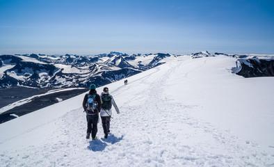 People hiking on top of Glittertind - the highest mountain in Jotunheimen, Norway. Galdhøpiggen seen in the horizon.