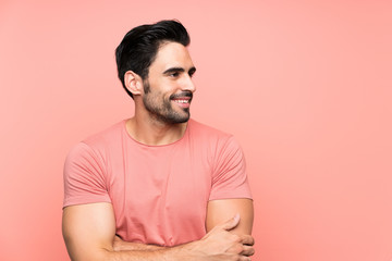 Handsome young man over isolated pink background looking to the side