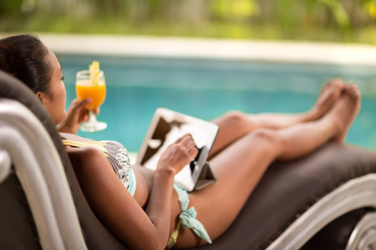 Woman using tablet by the swimming pool