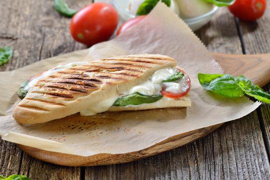 Panini  Caprese: Im Kontaktgrill gepresstes italienisches Panini mit Mozzarella, Tomaten und Basilikum - Pressed and toasted panini with buffalo cheese, tomatoes and basil fresh from the plate grill