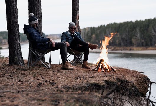 Male friends resting around bonfire by river