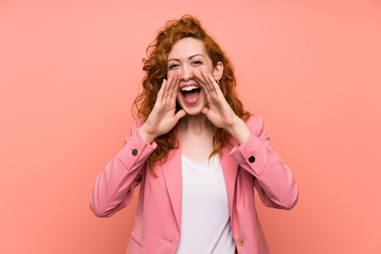 Redhead woman in suit over isolated pink wall shouting with mouth wide open