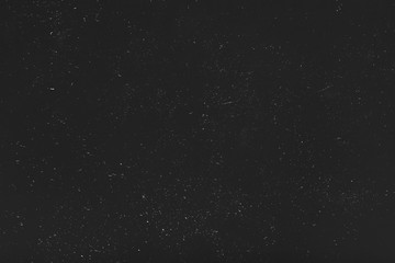Grunge distressed abstract background. White dust and scratches over black surface. Empty space.