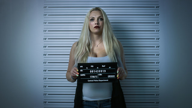 In Police Station Arrested Woman Posing for Front-View Mugshot. Wears Saucy Clothes, Has Smudged Heavy Makeup, Her Hair Is Disheveled and She Holds Placard. Height Chart in Background. Vignette Filter