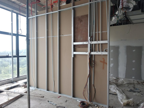 Drywall installation work in progress by construction workers at the construction site. It is the easiest and cheapest way to do partition for an interior wall.