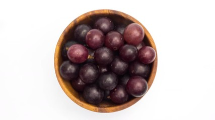 Fototapete - Put grapes into wooden bowl on white background in Stop Motion