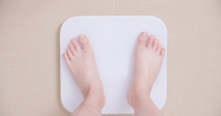 woman stand on weight scale