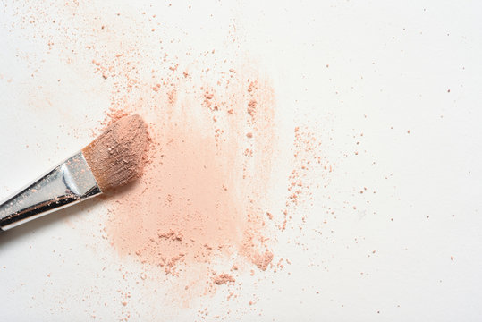 Pink make up spilled over white surface with make up brush covered in powder