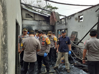 Police officers examine a house used as a factory producing matchsticks after a fire swept through, at Binjai district in Langkat