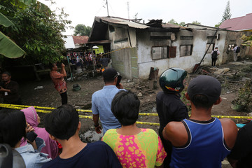 Locals look at a house used as a factory producing matchsticks after a fire swept through, at Binjai district in Langkat, North Sumatra province