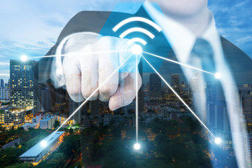 Businessman push wifi icon on city and network connection concept. Bangkok smart city and wireless communication network, abstract image visual, internet of things.