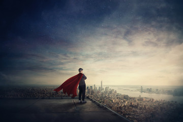 Businesswoman as confident superhero with red cape stands on the rooftop looking over city horizon. Ambition and business success concept.