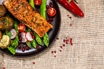 Grilled salmon, baked potatoes and vegetable salad