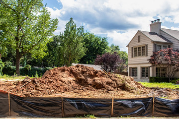 Construction  - Pile of dirt in vacant lot behind black plastic fence in upscale neighborhood with parts of adjacent houses and trees and fences visible - selective focus