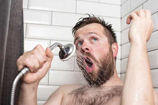 Cute bearded man singing in the bathroom using the shower head with flowing water instead of a microphone.