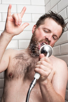 A bearded man sings in the bathroom, using a shower with running water instead of a microphone and showing rock n roll sign or giving the devil horns gesture.
