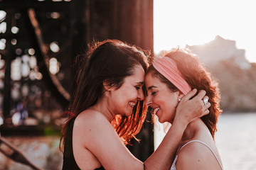 young lesbian couple hugging at sunset outdoors. Lifestyle and pride concept. love is love
