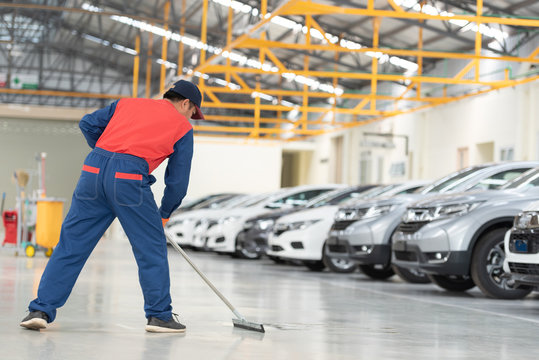 The man in the repairman is holding a mop in a white suit, cleaning the protective clothing of the new epoxy floor in an empty warehouse or car service center.