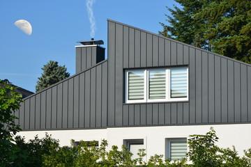 Fassaden- und Schornstein-Verkleidung eines modernen Wohngebäudes aus dunkelgrau beschichtetem Stehfalz-Metall und Fenster mit Sichtschutzstreifen,