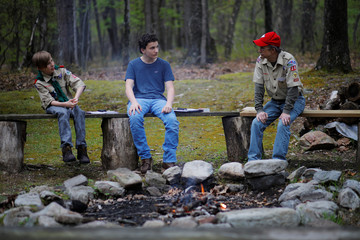 Boy Scouts from Troop 36 sit around a fire at their camp in Roseto