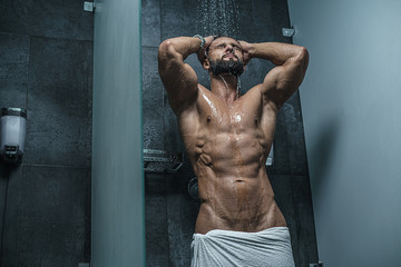 Sexy muscular man with naked torso in shower. Bodybuilder. Mature content