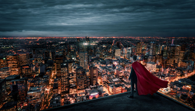 Businessman with red cape like a superhero standing on the rooftop and looking at the city ay night with copy space