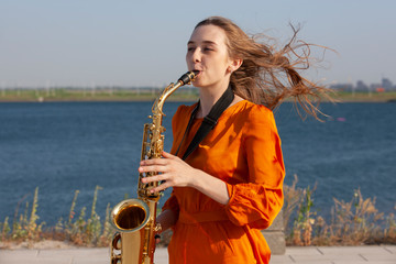 Young woman with saxophone with nature background