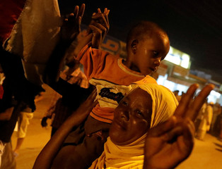 A Sudanese woman makes victory sign as she carries her baby during a demonstration in Khartoum