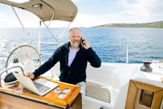 Digitaler Nomade mit Laptop telefoniert glücklich auf einem Segelboot