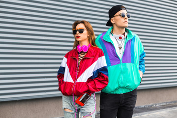 Back in time 90s 80s. Stylish young man in a retro jacket and a girl in red and with a vintage cassette player, against a steel wall, fashion trends, a street image