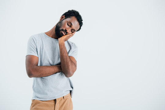 exhausted african american man sleeping on hand isolated on grey