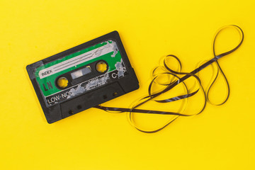 old retro cassette tape with grunge label surrounded by pulled tape pile on yellow background flat lay
