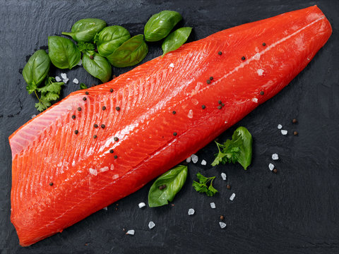 Fresh raw pacific wild sockeye salmon fillet on natural stone with spices and basil leaves