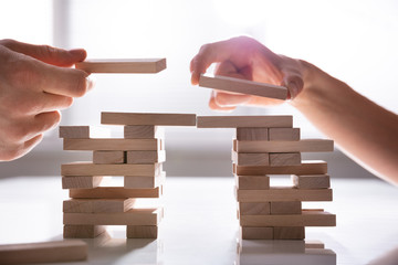 Human's Hand Placing Wooden Block