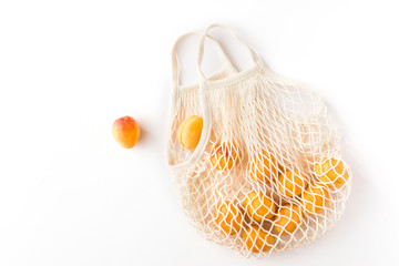 Top view of mesh shopping bag with organic eco fruits isolated on white background. Caring for the environment and the rejection of plastic concept