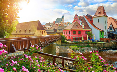 Fototapeta Czech Krumlov, (Cesky Krumlov), Czech Republic. Wooden bridge over river Vltava. Vintage picturesque old town with colorful houses and chapel of church. Rose flowers on bank. Sunny summer day.