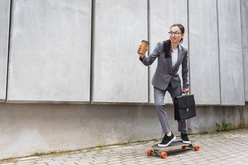 happy businesswoman in formal wear riding on skateboard, holding paper cup and briefcase in hands