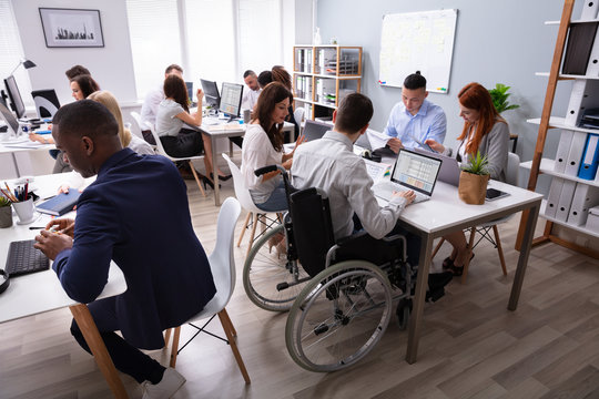 Disabled Businessman Sitting On Wheelchair Using Laptop